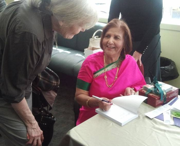 Shashi in sari signing a copy of her book